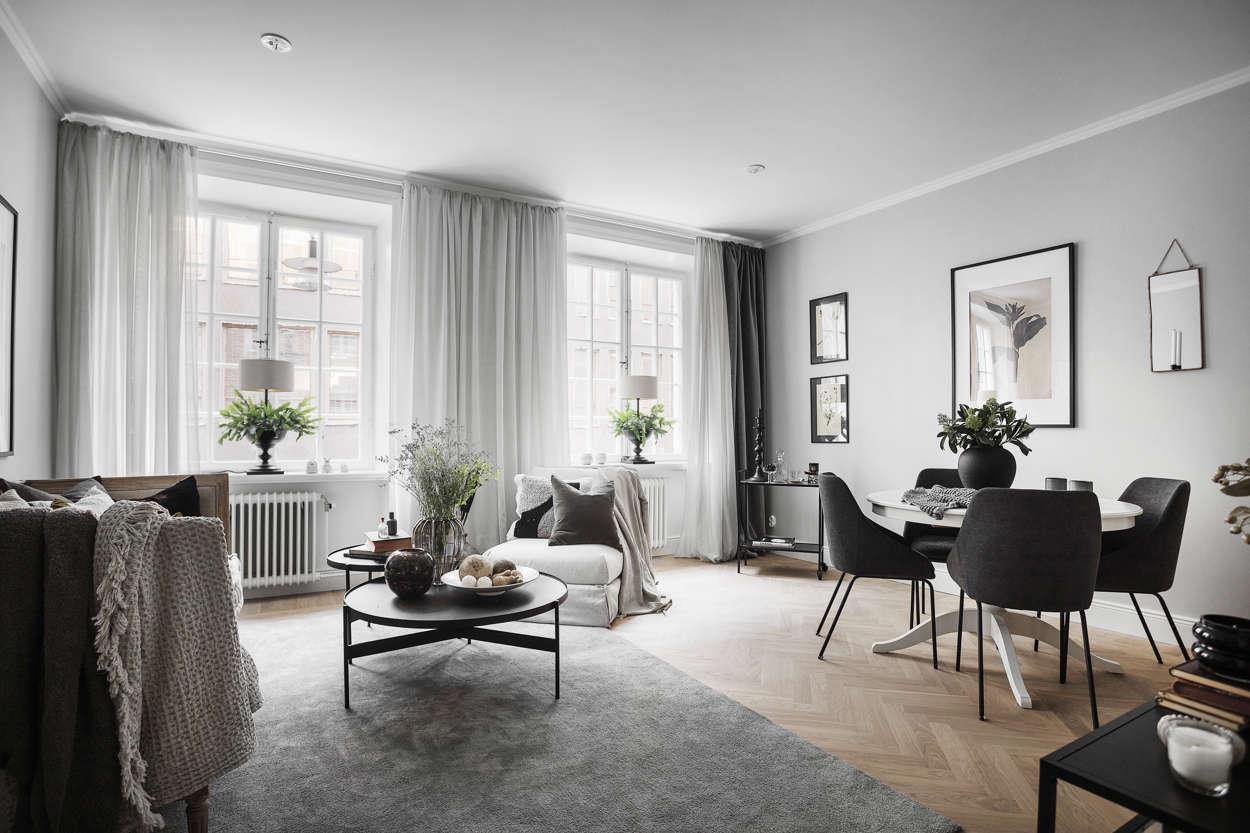 Ljust vardagsrum med vackra, spröjsade fönster