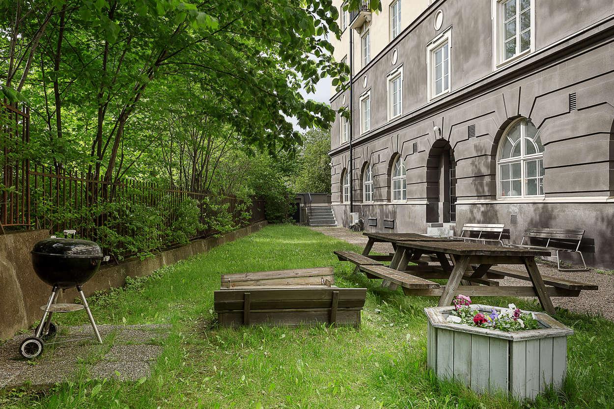 Bakgården med gräsmattor, utemöbler och sandlåda