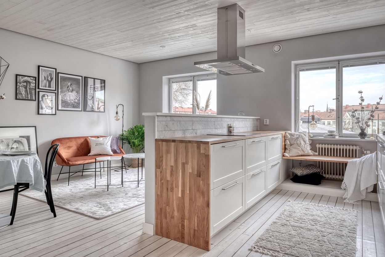 Vardagsrum och kök i öppen planlösning, generös takhöjd med infälld belysning & vackert originalgolv