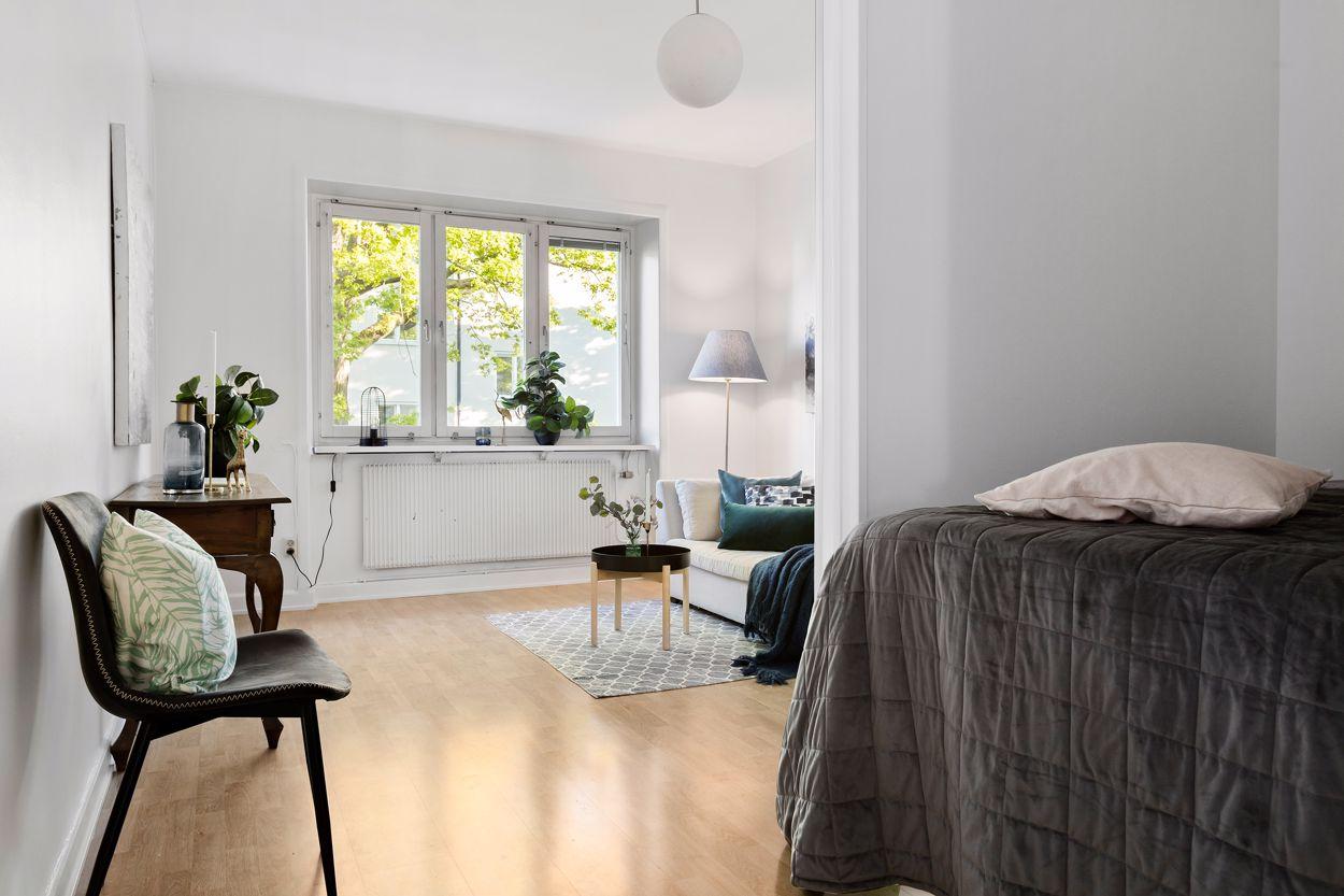 Vardagsrum med stort fönster och alkov